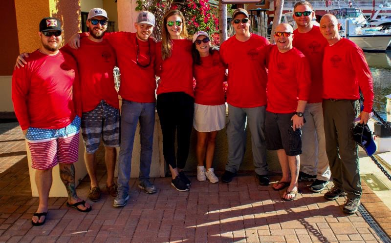 Event co-host Angie Skinner (fifth from left) joins service members participating in the 2018 Redfish Round-Up fishing tournament.