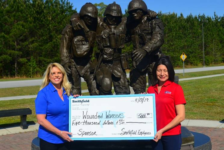 Rhonda Campbell with Smithfield Foods presents Raquel Painter of Hope For The Warriors with a $5,000 donation to the annual Hope For The Warriors Invitational event.